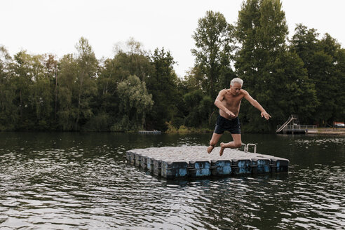 Senior man jumping from raft in a lake - GUSF01836