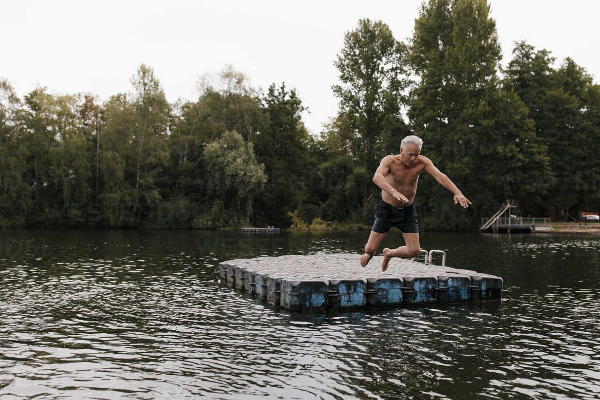 Senior man jumping from raft in a lake - GUSF01836 - Gustafsson/Westend61