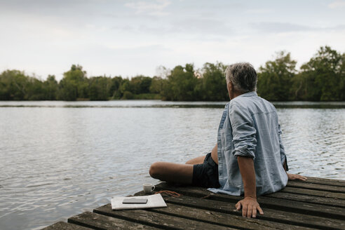 Senior man sitting on jetty at a lake - GUSF01839