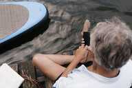 Senior man sitting on jetty at a lake using cell phone - GUSF01842