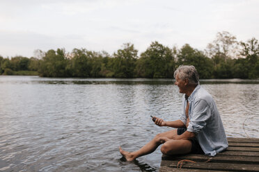 Happy senior man sitting on jetty at a lake with cell phone - GUSF01845