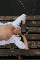 Senior man lying on jetty at a lake wearing VR glasses - GUSF01848