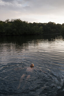 Senior man swimming in a lake at sunset - GUSF01851