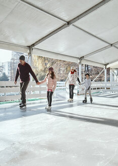 Family with two kids ice skating on the ice rink - ZEDF01790
