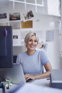 Young woman working in office, sitting at desk, smiling - PNEF01136