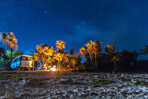 Mexico, Yucatán, Quintana Roo, Tulum, Camping Bus oder VW-Bus am Strand unter Palmen mit Lagerfeuer und Sternenhimmel. Glamping. - MMAF00775