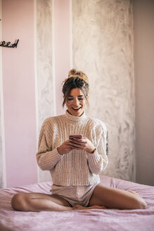 Portrait of young woman sitting on bed text messaging - ACPF00389