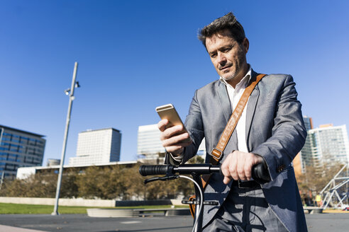 Mature businessman commuting in the city with his kick scooter, usine smartphone - GIOF05555
