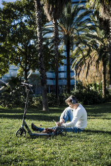 casual businessman sitting on grass in a park, using smartphone and headphones - GIOF05600