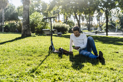 casual businessman sitting on grass in a park, using smartphone and headphones - GIOF05603