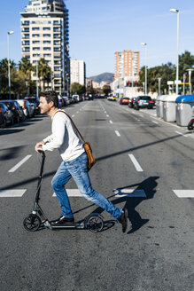 Mature man commuiting in the city with his kick scooter, crossing a street - GIOF05618