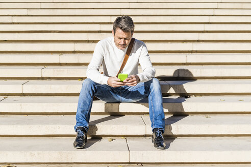 Casual businessman sitting on stairs, reading messages on his smartphone - GIOF05621