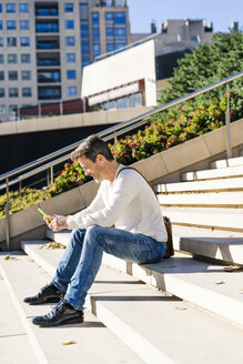 Casual businessman sitting on stairs, reading messages on his smartphone - GIOF05624