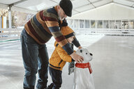 Grandfather and grandson on the ice rink, ice skating, using ice bear figure as prop - ZEDF01801