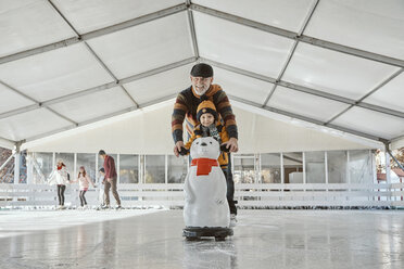 Grandfather and grandson on the ice rink, ice skating, using ice bear figure as prop - ZED01804