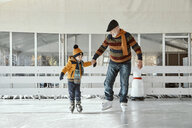 Grandfather and grandson on the ice rink, ice skating - ZEDF01807