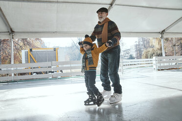 Grandfather and grandson on the ice rink, ice skating - ZEDF01810