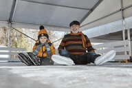 Serbia, Novi Sad, Ice skating, Grandfather and grandson, On the ground - ZEDF01813