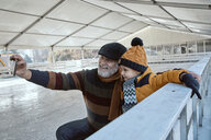 Grandfather and grandson on the ice rink, taking selfies - ZEDF01816