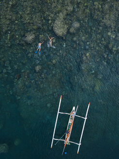 Couple snorkeling in ocean, next to banca boat - KNTF02615