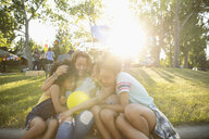 Affectionate mother and daughters hugging at summer neighborhood block party in sunny park - HEROF06160
