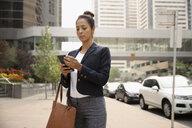 Businesswoman using smart phone on city sidewalk - HEROF06184