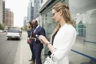 Business people using smart phones on city sidewalk - HEROF06268