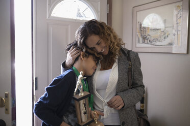 Affectionate Latinx mother hugging son holding sports trophy - HEROF06337