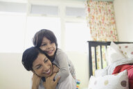 Mother and son hugging in bedroom - HEROF06355