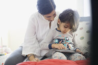 Mother and son using digital tablet on bed - HEROF06364