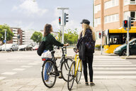 Two young women pushing bikes in town - ASTF02471