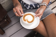 Woman holding coffee cup with cappuccino - ASTF02519