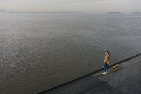 Germany, Hamburg, top view of woman standing on pier at the Elbe shore - JOSF02879