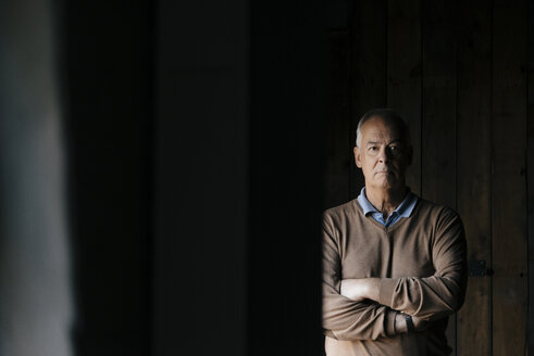 Portrait of serious senior businessman in front of wooden wall - JOSF02885