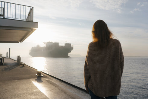 Germany, Hamburg, woman standing on pier at the Elbe shore with container ship in background - JOSF02888