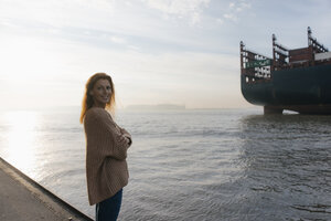 Germany, Hamburg, woman standing on pier at the Elbe shore with container ship in background - JOSF02891