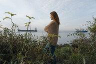 Germany, Hamburg, woman standing at the Elbe shore - JOSF02894