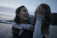 Germany, Hamburg, two happy teenage girls hugging on the beach at Elbe shore in the evening - JOSF02900