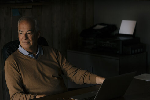 Senior businessman with laptop sitting at desk in office - JOSF02909