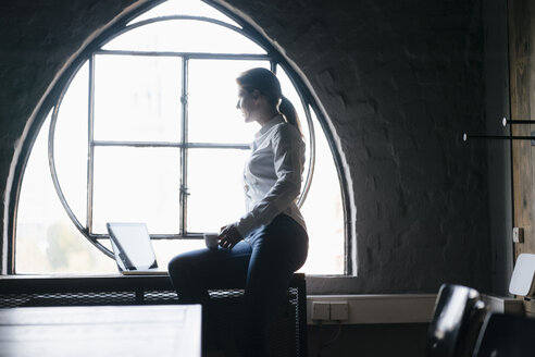 Businesswoman with laptop and cup of coffee at the window - JOSF02912