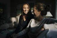 Two happy teenage girls with cell phone sitting on couch at home - JOSF02942