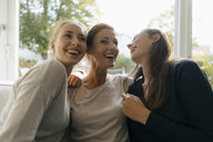 Happy mother with two teenage girls on couch at home - JOSF02948