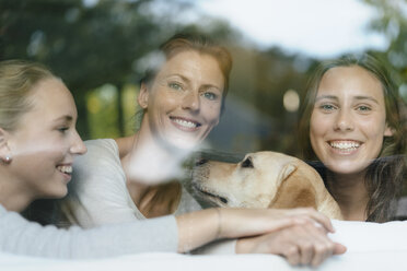 Portrait of happy mother with two teenage girls and dog behind windowpane - JOSF02954