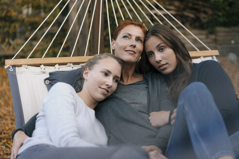 Happy mother with two teenage girls lying in hammock in garden in autumn - JOSF02960