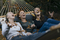 Carefree mother with two teenage girls throwing autumn leaves in hammock in garden - JOSF02966