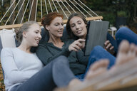 Happy mother with two teenage girls lying in hammock in garden in autumn using tablet - JOSF02969