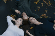 Mother with two teenage girls lying on trampoline in autumn - JOSF02972