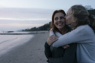 Germany, Hamburg, mother and teenage girl hugging on the beach at Elbe shore in the evening - JOSF02978