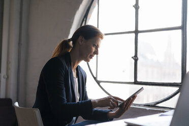 Businesswoman using tablet at the window in office - JOSF02996