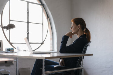 Businesswoman with laptop sitting at desk in office - JOSF02999